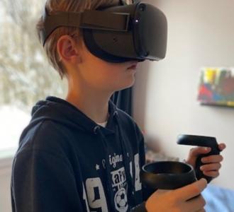 poika pelaamassa virtuaalilasit päässä.